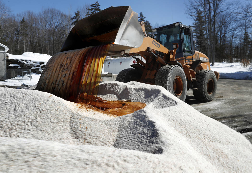 "David Osgood, crew leader of the public works deptartment, mixes ""Ice-B-Gone,"" into a pile of road salt, Monday, March 12, 2018, in Freeport, Maine. The liquid, a by-product of vodka, he ..."