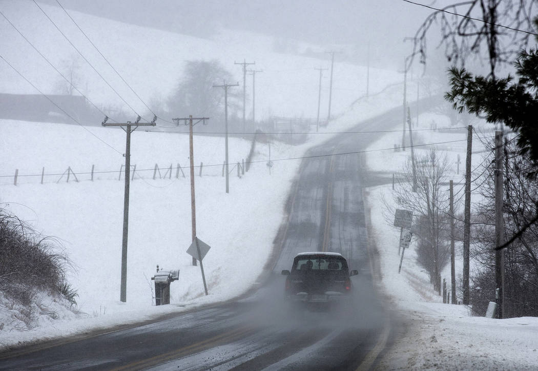 A vehicle drives through snow on Bent Mountain Road near Snake Drive in Copper Hill, Floyd County, Va., Monday, March 12, 2018. (Erica Yoon /The Roanoke Times via AP)