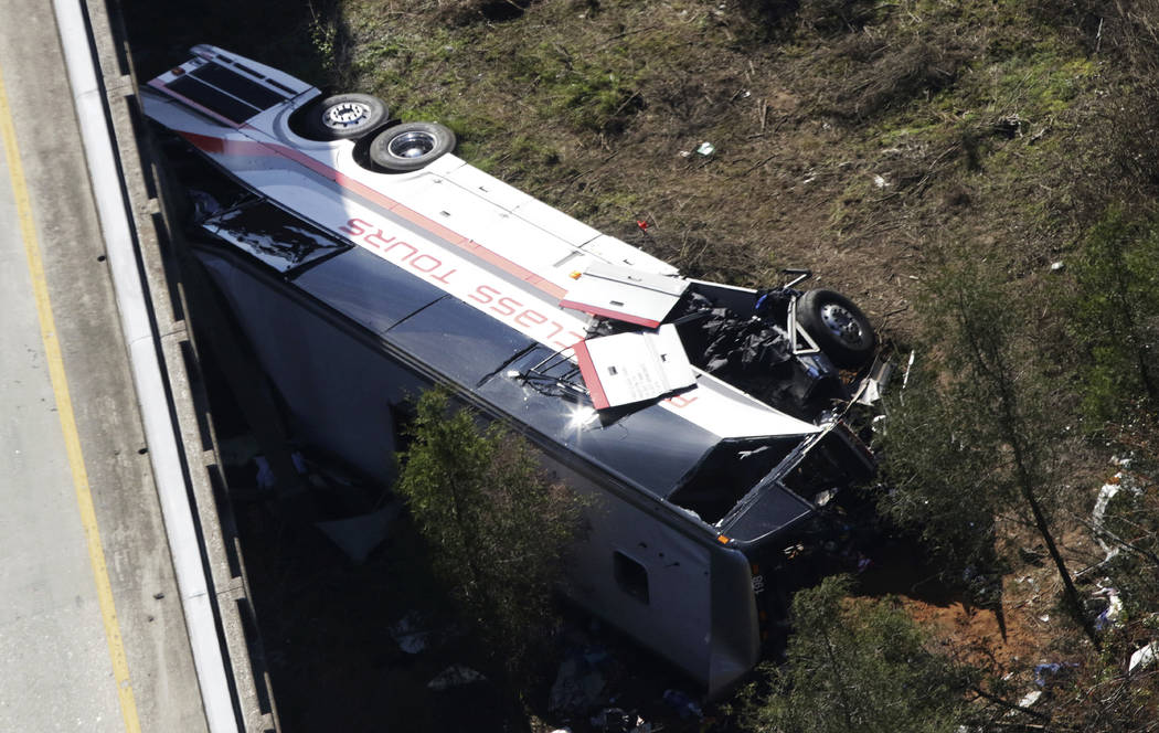 A charter bus sits in a ravine after a deadly crash on Tuesday, March 13, 2018, in Loxley, Ala. The bus carrying Texas high school band members home from Disney World plunged into the ravine befor ...