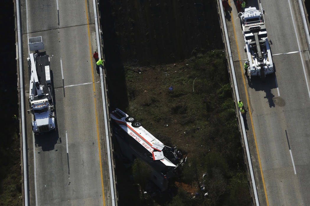 Rescue crews look down on a charter bus after a crash on Tuesday, March 13, 2018, in Loxley, Ala. The bus carrying Texas high school band members home from Disney World plunged into a ravine befor ...