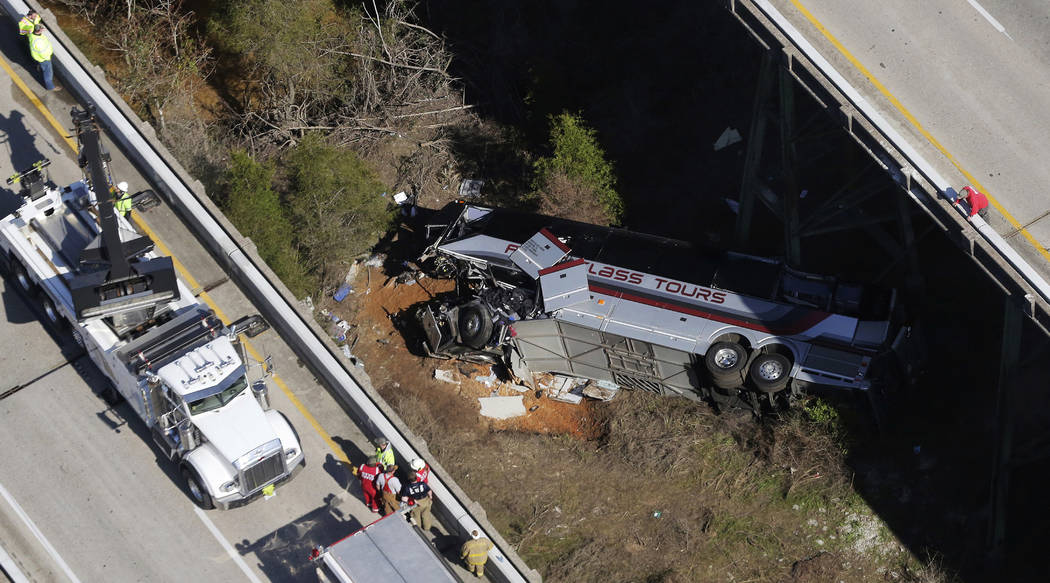 Rescue crews work at the scene of a deadly charter bus crash on Tuesday, March 13, 2018, in Loxley, Ala. The bus carrying Texas high school band members home from Disney World plunged into a ravin ...