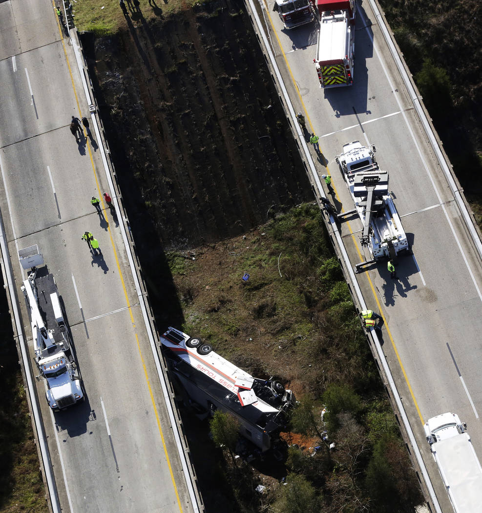 Rescue crews look down on a charter bus after a deadly crash on Tuesday, March 13, 2018, in Loxley, Ala. The bus carrying Texas high school band members home from Disney World plunged into a ravin ...