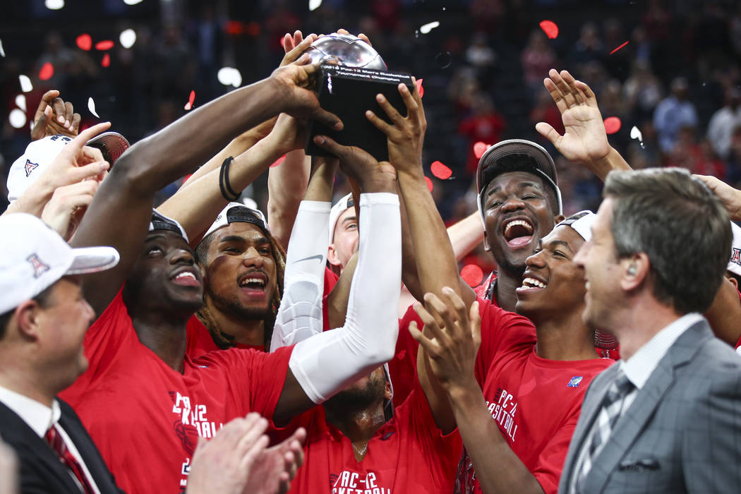 Arizona Wildcats players lift up their trophy after their defeat over the USC Trojans in the Pac-12 tournament championship basketball game at T-Mobile Arena in Las Vegas on Saturday, March 10, 20 ...