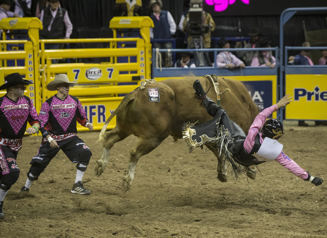 Sage Kimzey is thrown from Spin Bo during the bull riding competition at the National Finals Rodeo at the Thomas & Mack Center on Monday, Dec. 5, 2016, in Las Vegas. (Benjamin Hager/Las Vegas Revi ...