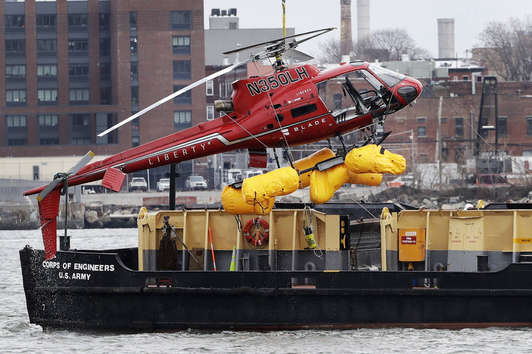A helicopter is hoisted by crane from the East River onto a barge, Monday, March 12, 2018, in New York. The pilot was able to escape the Sunday night crash after the aircraft flipped upside down i ...