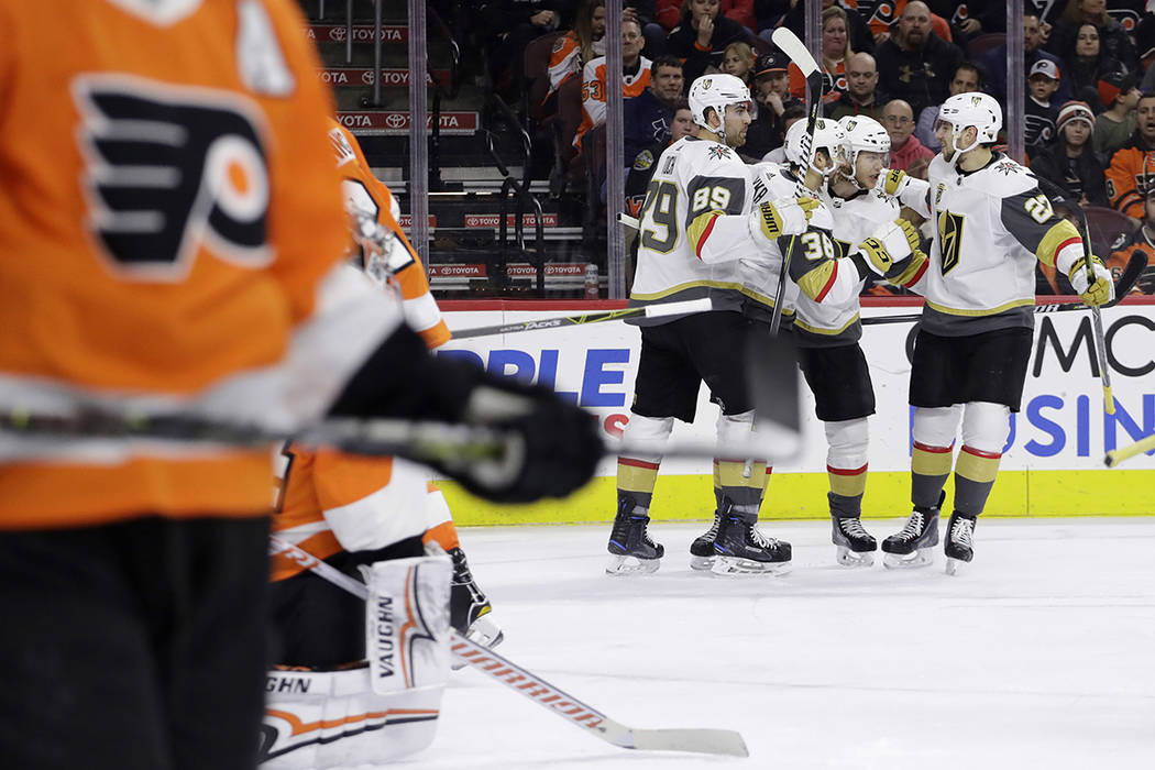 Vegas Golden Knights' Shea Theodore (27), William Karlsson (71), Tomas Hyka (38) and Alex Tuch (89) celebrate after a goal by Karlsson during the third period of an NHL hockey game against the Phi ...