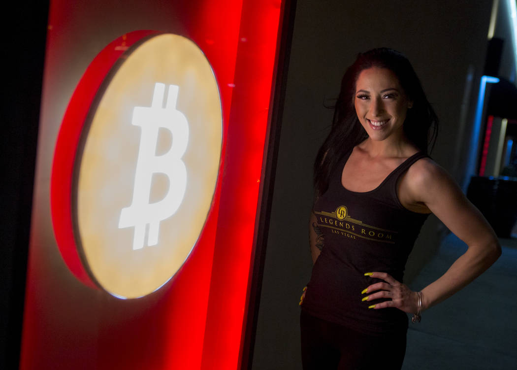 Bartender Deianna Lo next to the club's Bitcoin sign outside of the Legends Room in Las Vegas on Wednesday, March 21, 2018. Patrick Connolly Las Vegas Review-Journal @PConnPie