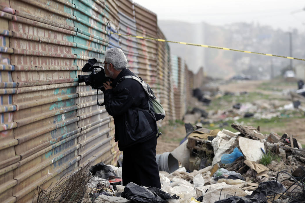 A journalist peers through a hole in the current border wall on the Mexico side of the border on Tuesday, March 13, 2018, in Tijuana, Mexico. President Trump is scheduled to visit the site of the  ...