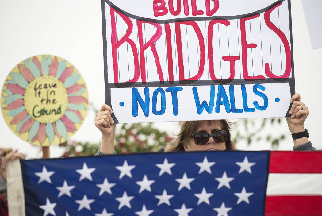 "Lauren Rees holds up a sign during a rally against a upcoming scheduled visit by President Donald Trump Tuesday, March 13, 2018, in San Diego.  Protesters chanted, ""No ban! No wall!"" ..."