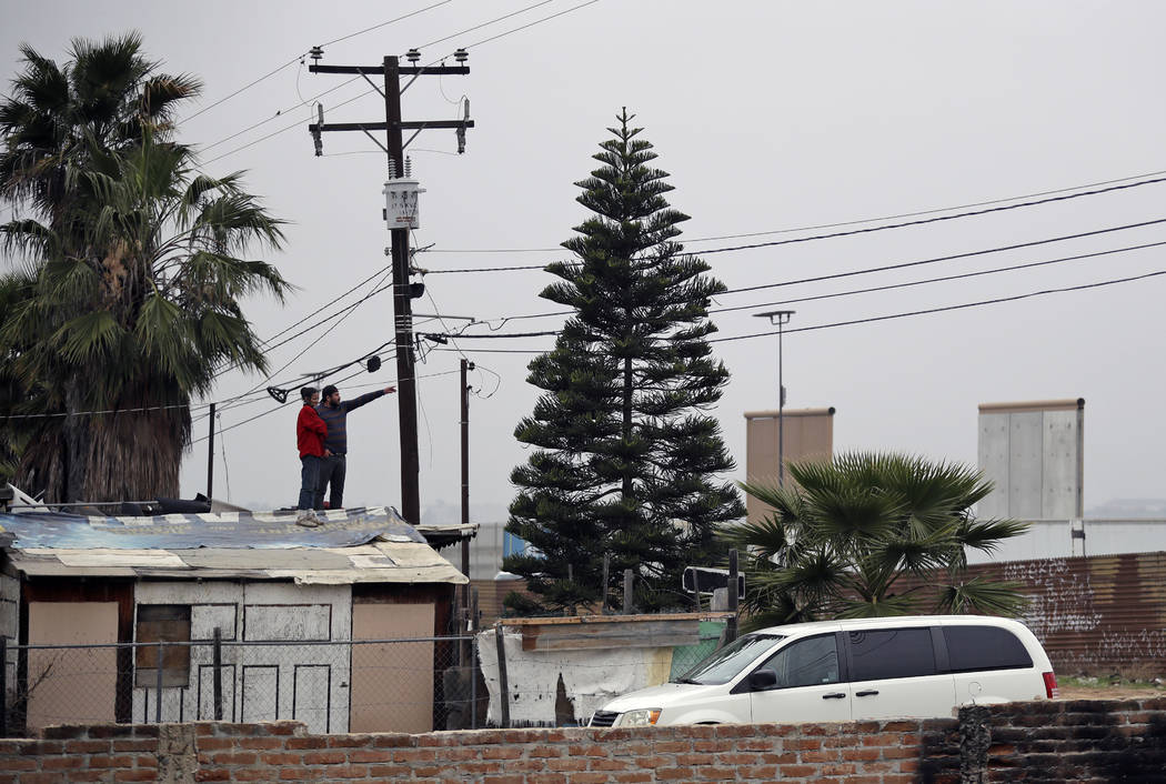 A couple stand on a rooftop on the Mexico side to look over to the U.S. side of the border on Tuesday, March 13, 2018, in Tijuana, Mexico. President Trump is scheduled to visit the site of the bor ...