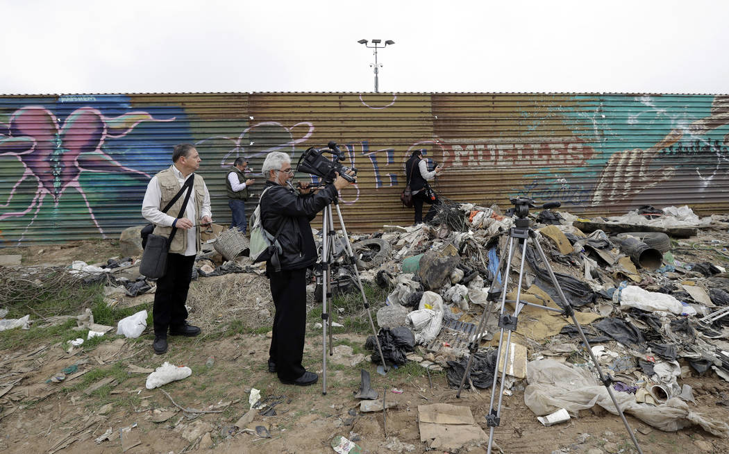 Journalists peer through a hole in the current border wall on the Mexico side of the border on Tuesday, March 13, 2018, in Tijuana, Mexico. President Trump is scheduled to visit the site of the bo ...