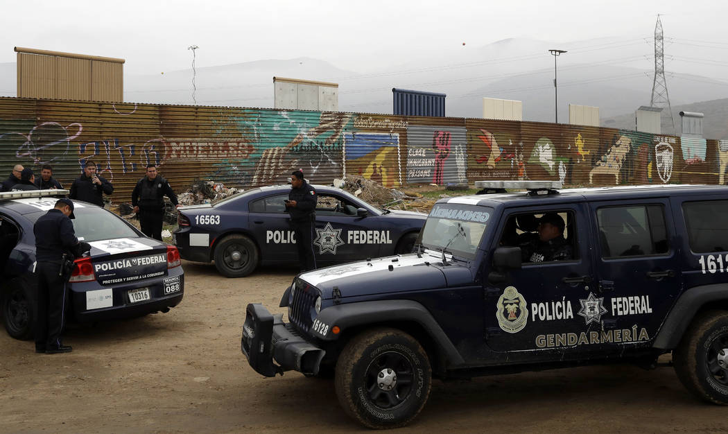 Mexican federal police officers stand guard on the Mexico side of the border on Tuesday, March 13, 2018, in Tijuana, Mexico. President Trump is scheduled to visit the site of the border wall proto ...