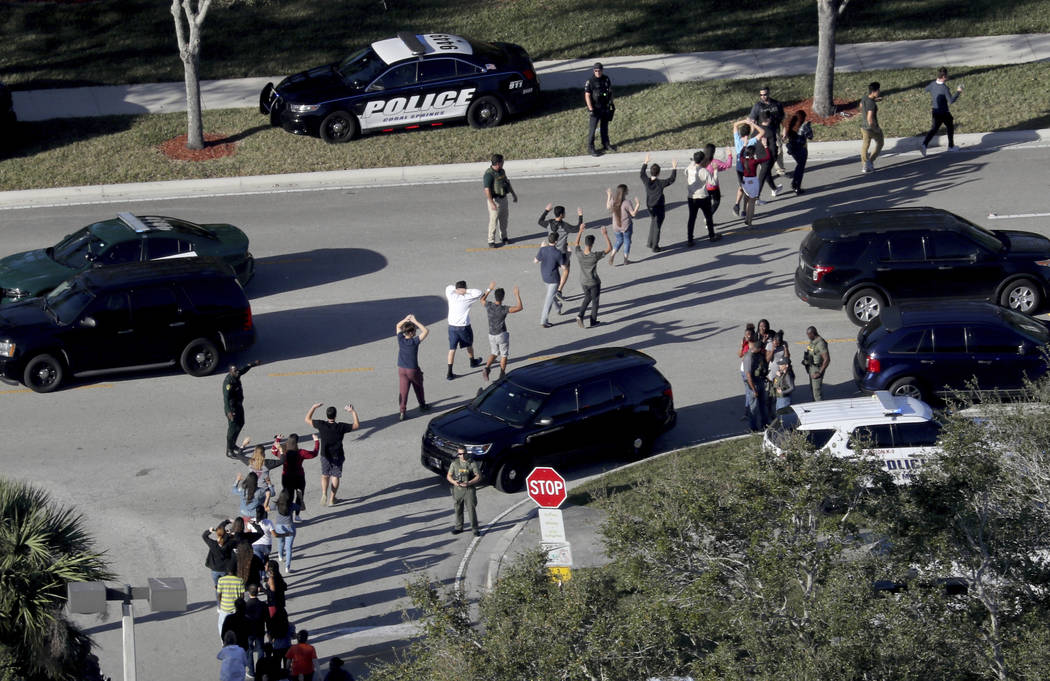 FILE - In this Feb. 14, 2018 file photo,  students hold their hands in the air as they are evacuated by police from Marjory Stoneman Douglas High School in Parkland, Fla., after a shooter opened f ...