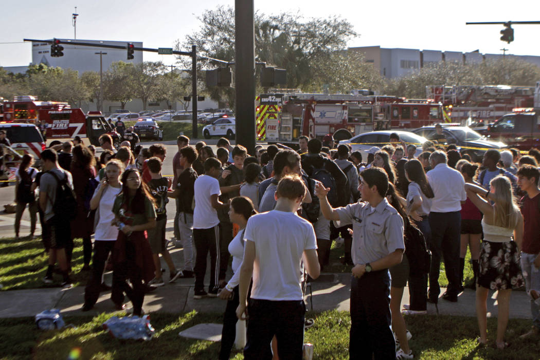 Students are released from a lockdown following a shooting at Marjory Stoneman Douglas High School in Parkland, Fla., on Wednesday, Feb. 14, 2018. (John McCall/South Florida Sun-Sentinel via AP)