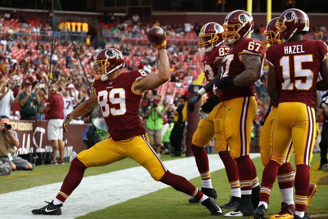 Washington Redskins tight end Derek Carrier spikes the ball in front of teammates after scoring a touchdown in the second half of a preseason NFL football game against the Cincinnati Bengals