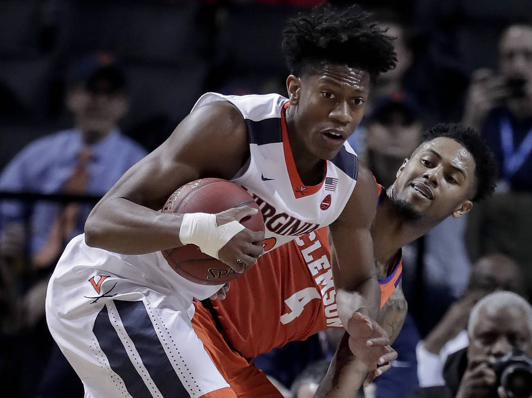 In this Friday, March 9, 2018, file photo, Virginia guard De'Andre Hunter (12) pulls down a rebound next to Clemson guard Shelton Mitchell (4) during the first half of an NCAA college basketball g ...