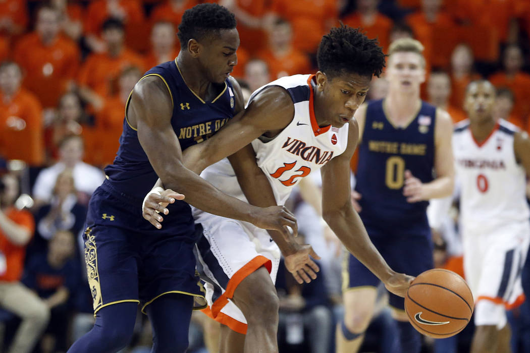 Virginia guard De'Andre Hunter (12) is fouled by Notre Dame forward Juwan Durham (11) during the second half of an NCAA college basketball game in Charlottesville, Va., Saturday, March 3, 2018. Vi ...