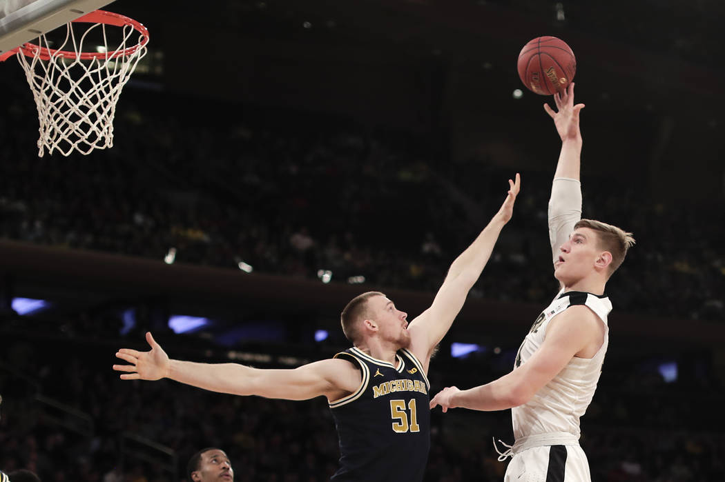 Purdue center Isaac Haas (44) puts up a shot against Michigan forward Austin Davis (51) during the first half of the NCAA Big Ten Conference tournament championship college basketball game, Sunday ...
