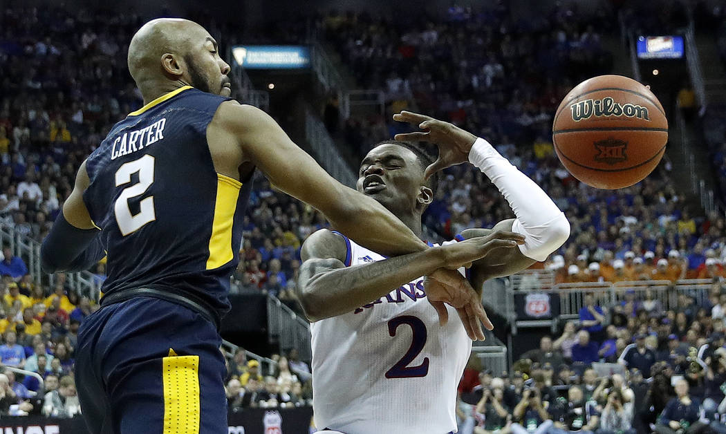 West Virginia's Jevon Carter knocks the ball away from Kansas' Lagerald Vick during the second half of the NCAA college basketball championship game in the Big 12 men's tournament Saturday, March  ...