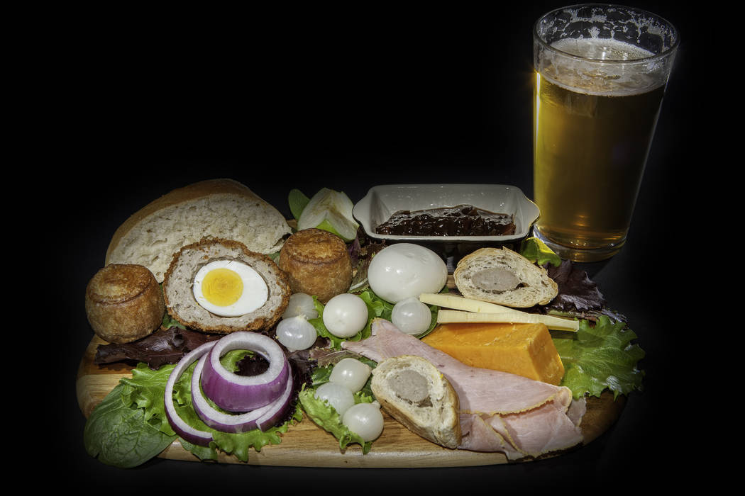 Ploughman?'s pub lunch including scotch egg; pork pies, ham; pickled onions and cheese served with a pint of lager beer. Isolated against a black background.