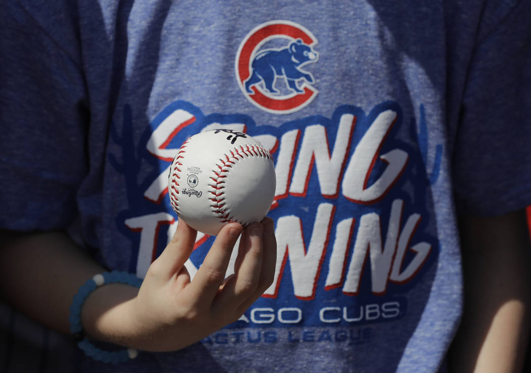 A fan holds a baseball before a spring training baseball game between the Colorado Rockies and the Chicago Cubs, Monday, March 20, 2017, in Scottsdale, Ariz. (AP Photo/Darron Cummings)