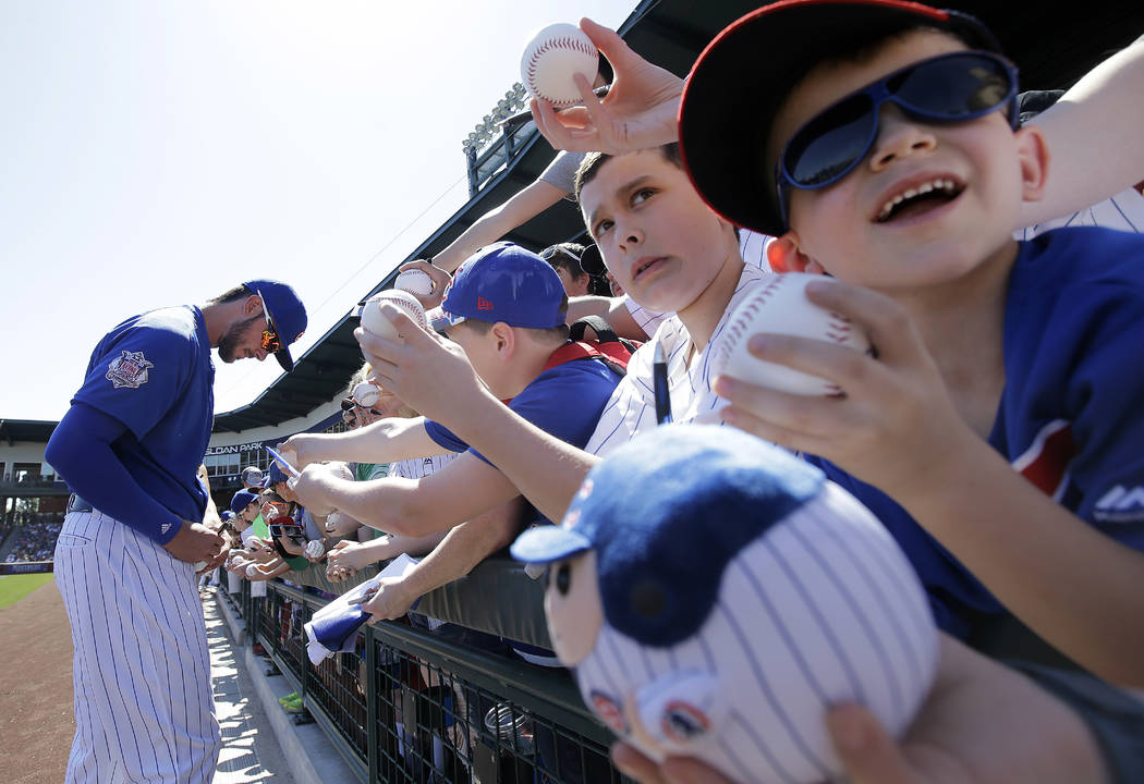 Chicago Cubs third baseman Kris Bryant signs autographs for fans before a spring training baseball game against the Milwaukee Brewers in Mesa, Ariz., Friday, March 25, 2016. (AP Photo/Jeff Chiu)