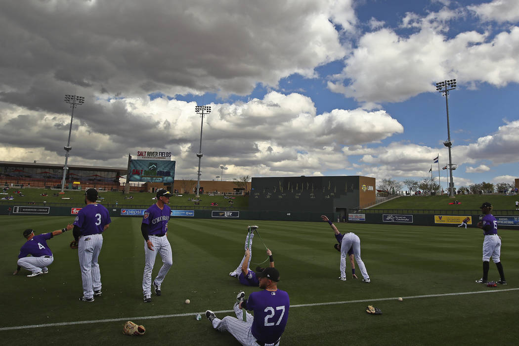 Colorado Rockies stretch before a spring training exhibition baseball game against the Arizona Diamondbacks on Friday, Feb. 23, 2018, in Scottsdale, Ariz. (AP Photo/Ben Margot)