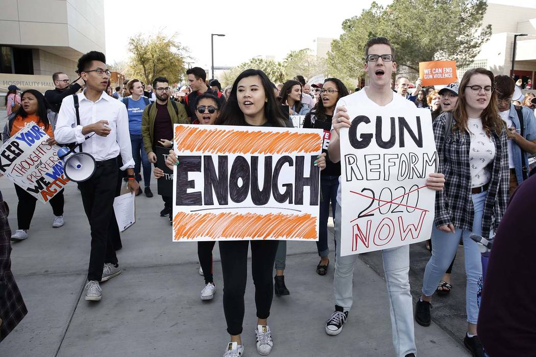 UNLV students, including Karl Catarata, second left, Tiffany Alm, center, and Aron Csiki shout slogans as they march on  campus in Las Vegas on Wednesday, March 14, 2018, as part of a nationwide p ...