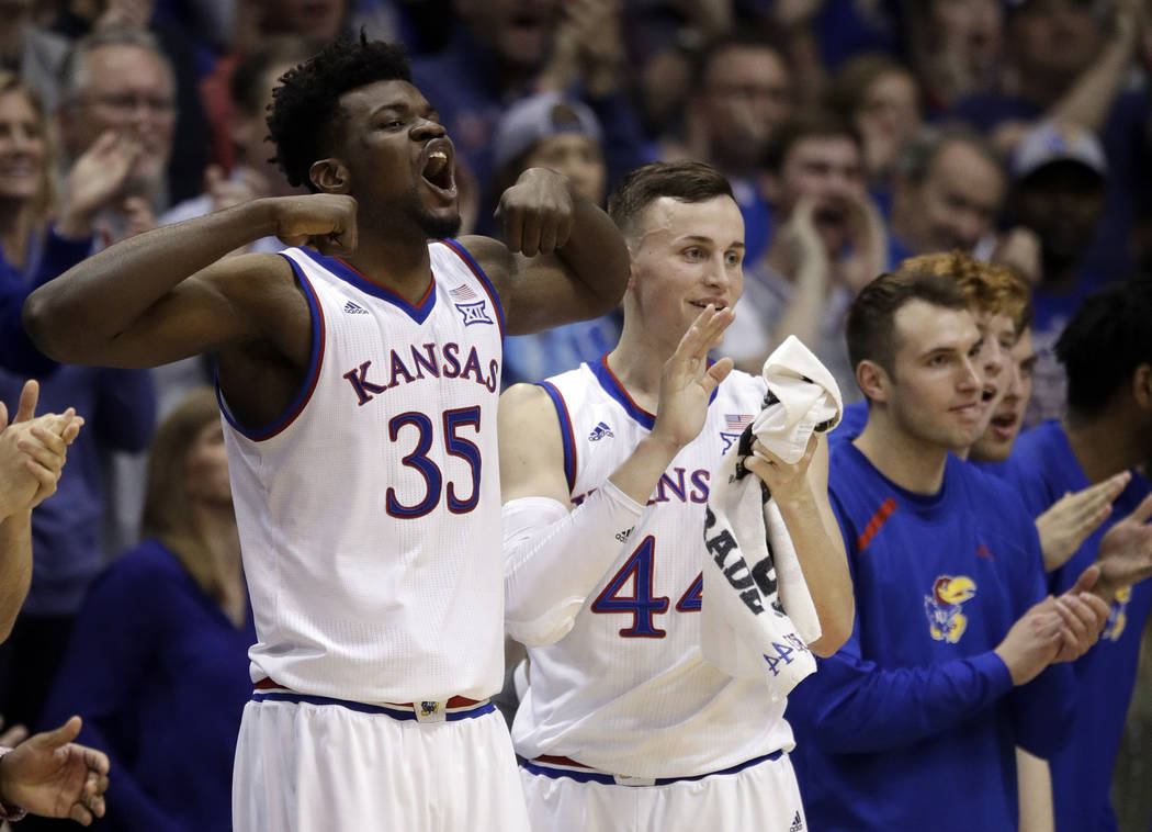 Kansas center Udoka Azubuike (35) and Kansas forward Mitch Lightfoot (44) celebrate a basket from the bench during the second half of an NCAA college basketball game against Oklahoma in Lawrence,  ...