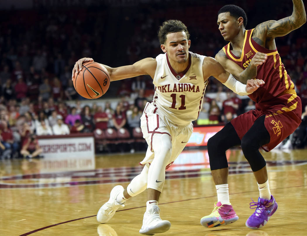 OKlahoma's Trae Young, left, drives past Iowa State's Donovan Jackson, right, in the second half of an NCAA college basketball game Friday, March 2, 2018, in Norman, Okla. (AP Photo/Kyle Phillips)