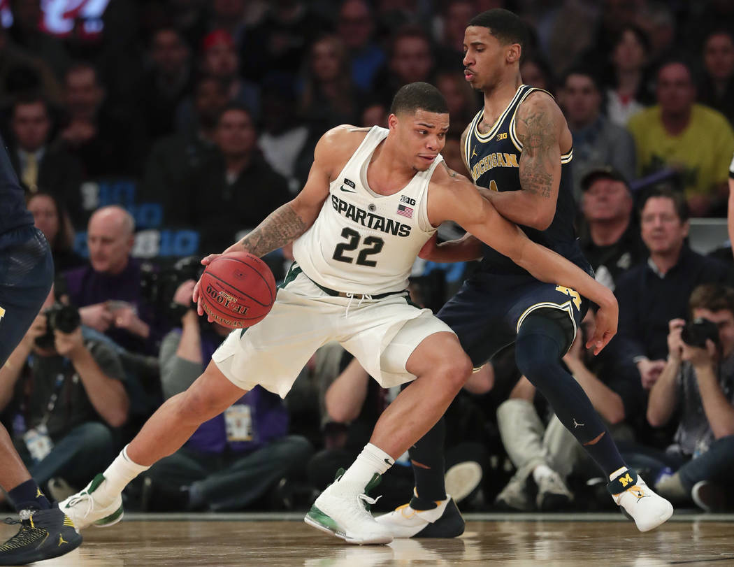 Michigan State guard Miles Bridges (22) drives against Michigan guard Charles Matthews (1) during the second half of an NCAA Big Ten Conference tournament semifinal college basketball game, Saturd ...