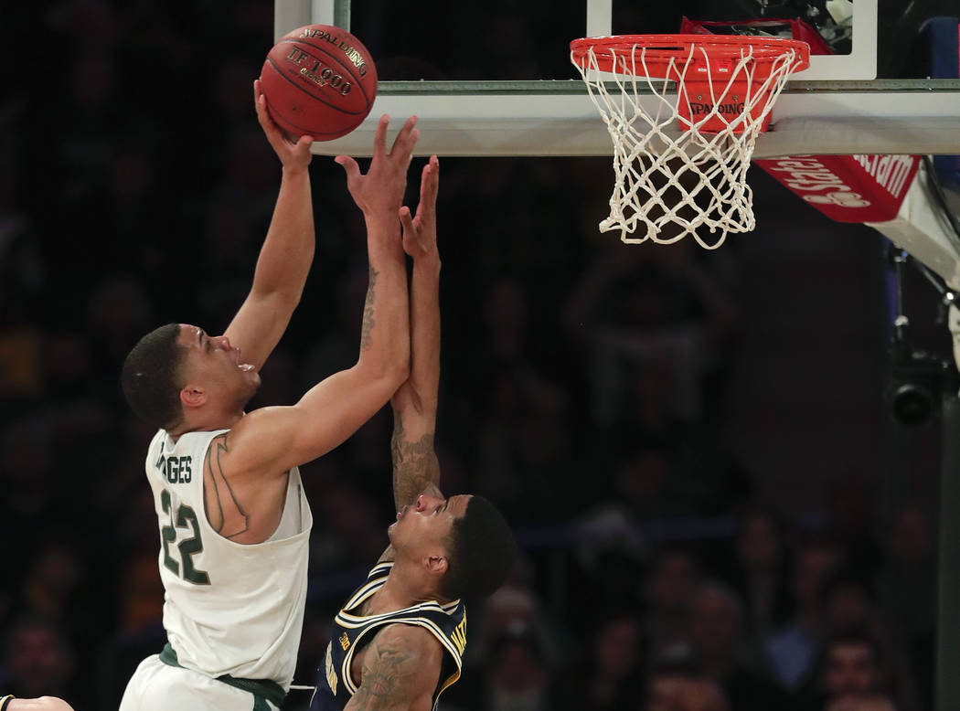 Michigan State guard Miles Bridges (22) puts up a shot against Michigan guard Charles Matthews (1) during the second half of an NCAA Big Ten Conference tournament semifinal college basketball game ...