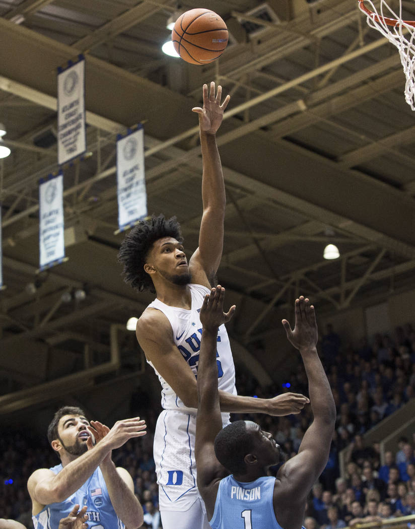 Duke's Marvin Bagley III (35) shoots over North Carolina's Theo Pinson (1) and North Carolina's Luke Maye, left, during the first half of an NCAA college basketball game in Durham, N.C., Saturday, ...