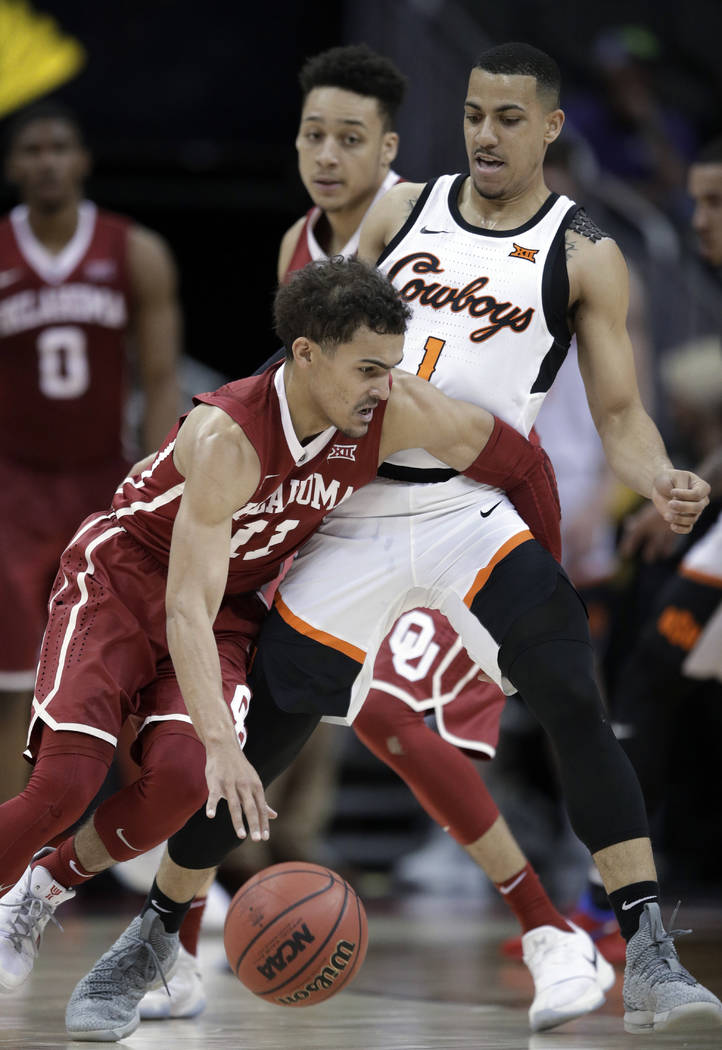 Oklahoma guard Trae Young (11) works around Oklahoma State guard Kendall Smith (1) during the first half of an NCAA college basketball game in first round of the Big 12 men's tournament in Kansas  ...