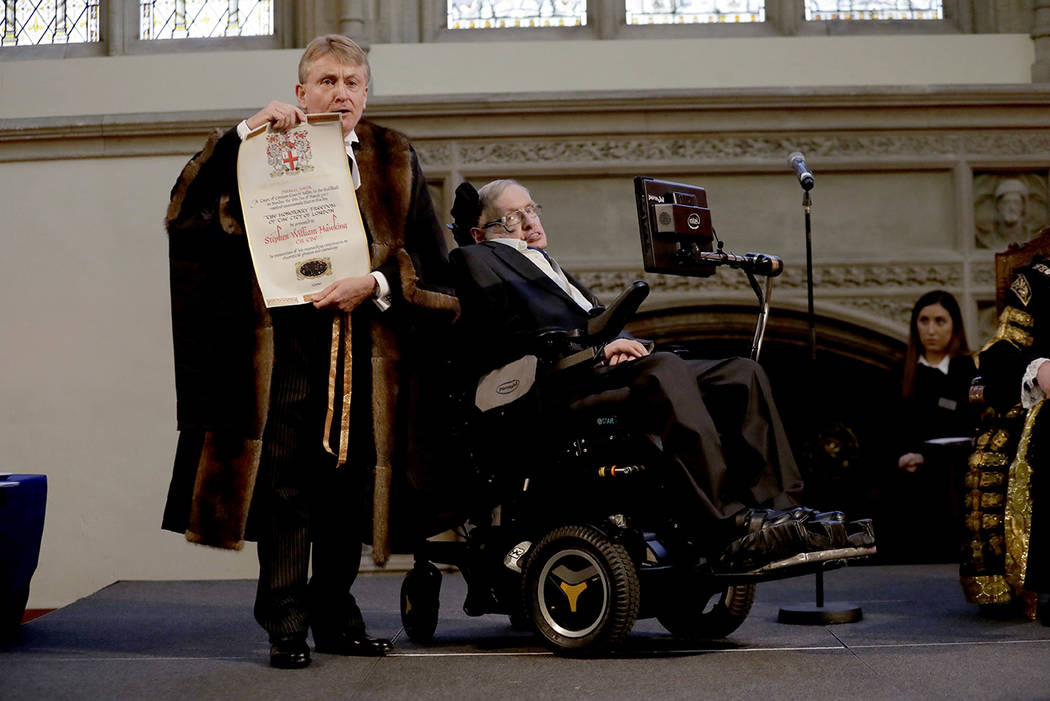 In this March 6, 2017 file photo, Britain's Professor Stephen Hawking is presented with his illuminated Freedom scroll by the Chamberlain of the City of London Peter Kane as he receives the Honora ...