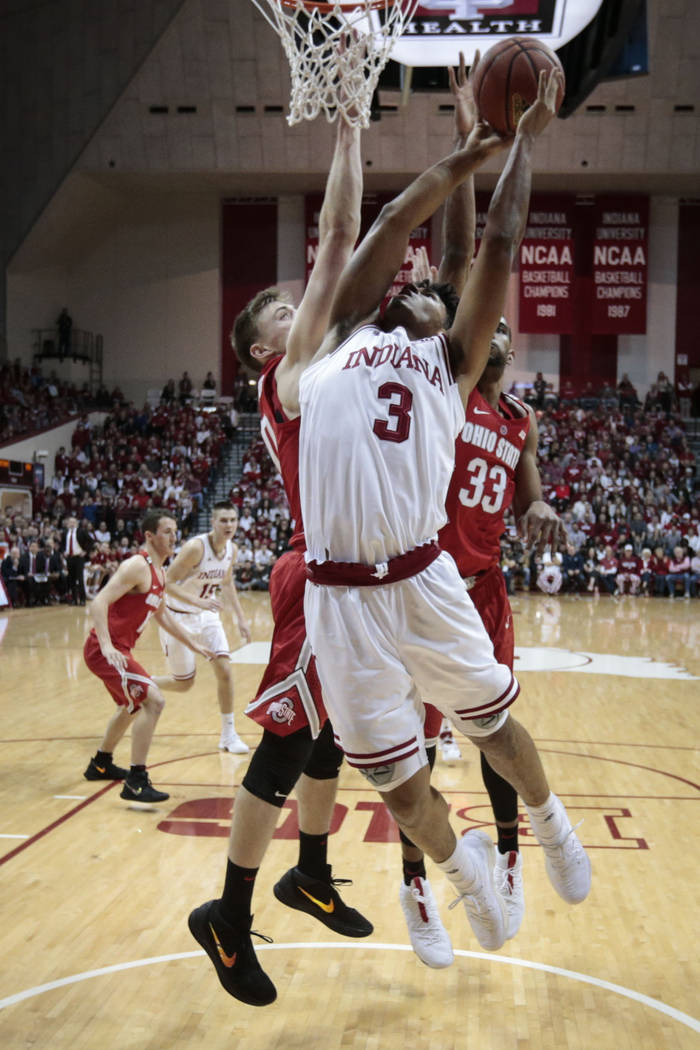 Indiana forward Justin Smith, center, goes to the basket in front of Ohio State center Micah Potter, left, and forward Keita Bates-Diop during the first half of an NCAA college basketball game in  ...