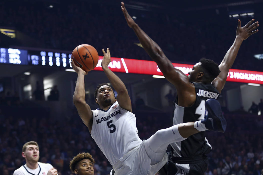 Xavier Trevon Bluiett takes a shot as he is fouled by Providence's Isaiah Jackson during the first half of an NCAA college basketball game, Wednesday, Feb. 28, 2018, in Cincinnati. (AP Photo/Aaron ...