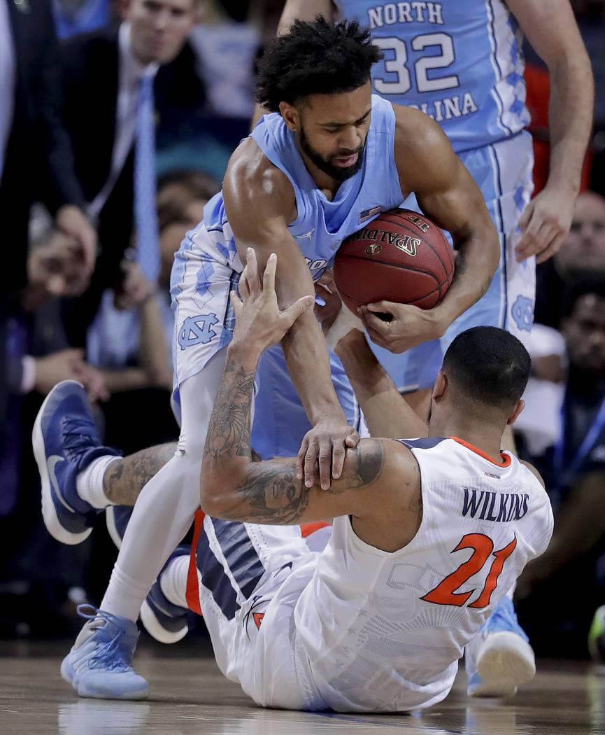 North Carolina guard Joel Berry II (2) becomes entangled with Virginia forward Isaiah Wilkins (21) while scrambling for the ball in the first half of an NCAA college basketball game during the cha ...