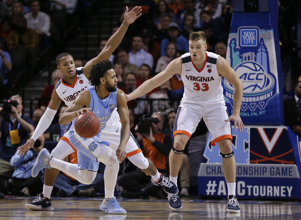 North Carolina guard Joel Berry II (2) drives against Virginia guard Devon Hall and center Jack Salt (33) during the second half of an NCAA college basketball game for the Atlantic Coast Conferenc ...