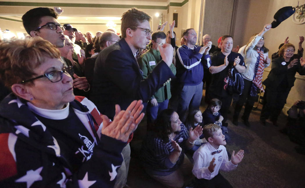 Bobbi Bauer, left, Khalid Husain, top, and Demetrios Germanos, center, celebrate with the crowd as results on the television say Republican Rick Saccone was closing the gap to under 1 percent of t ...