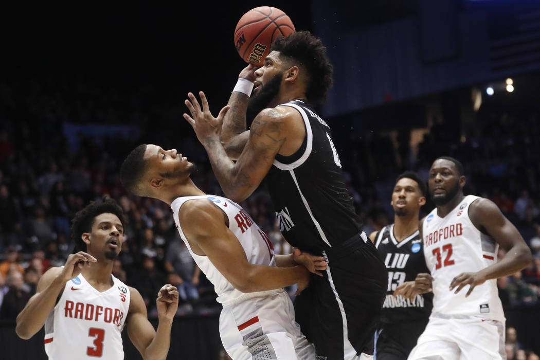 LIU Brooklyn's Joel Hernandez, center right, shoots against Radford's Travis Fields Jr. during the first half of a First Four game of the NCAA men's college basketball tournament, Tuesday, March 1 ...