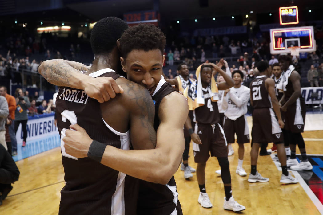St. Bonaventure's Jaylen Adams, center, hugs Matt Mobley (2) after their First Four game of the NCAA men's college basketball tournament against UCLA, Tuesday, March 13, 2018, in Dayton, Ohio. St. ...