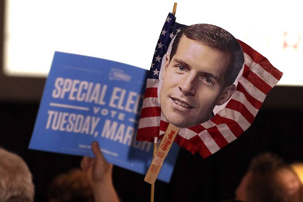 Supporters of Conor Lamb, the Democratic candidate for the March 13 special election in Pennsylvania's 18th Congressional District, hold signs during his election night party in Canonsburg, Pa., W ...