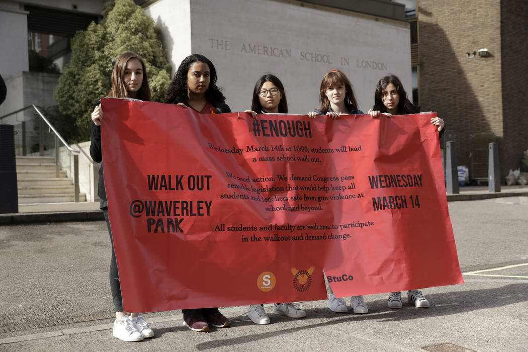 Students, aged 17 & 18, pose for photographs with a banner outside the front of the American School in London, after taking part in a 10am local-time, 17-minute walkout in the school playgroun ...