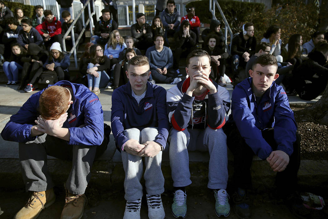 FILE - In this Feb. 28, 2018, file photo, Somerville High School students sit on the sidewalk on Highland Avenue during a student walkout at the school in Somerville, Mass. A large-scale, coordina ...