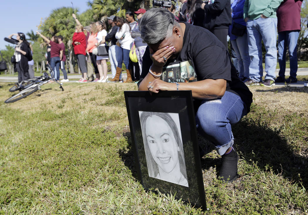 Pat Gibson holds a drawing of Meadow Pollack, a victim of the Marjory Stoneman Douglas High School shooting, as she stands outside of the school as part of a nationwide protest against gun violenc ...