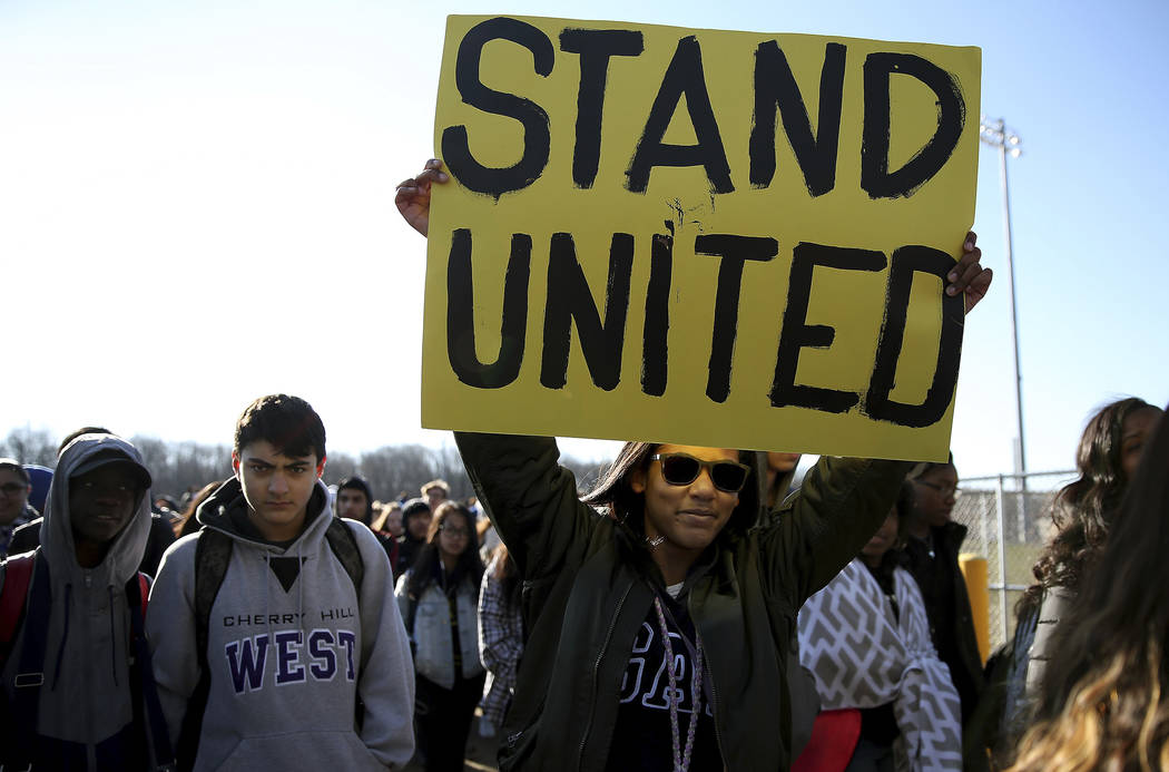 Freshman Kennedi Lawson, 14, carries a sign as student walkout at Cherry Hill West High School in remembrance of those killed in the Parkland, Fla., shooting in Cherry Hill, N.J., on Wednesday, Ma ...