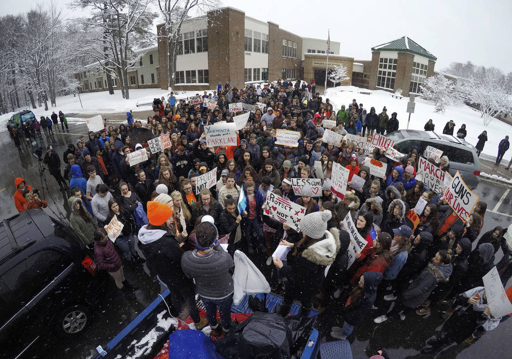 Students at Yarmouth High School participate in a walkout to protest gun violence, Wednesday, March 14, 2018, in Yarmouth, Maine. Leaders of the rally address the crowd from the back of a pick-up  ...