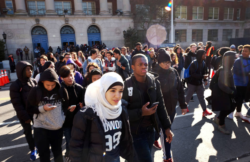 Hundreds of students walk out of Midwood High School as part of a nationwide protest against gun violence, Wednesday, March 14, 2018, in the Brooklyn borough of New York. It is the nation's bigges ...