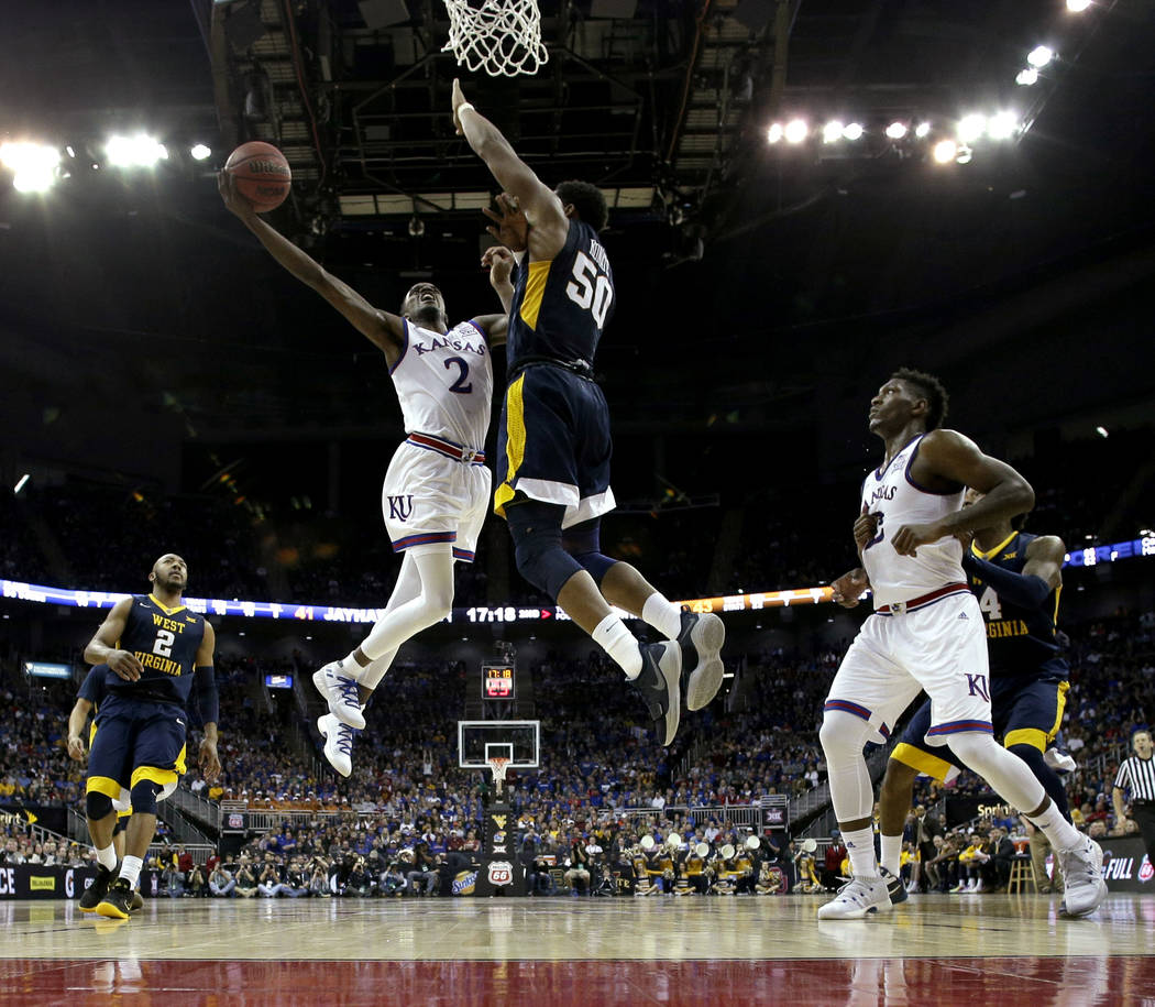 Kansas' Lagerald Vick (2) puts up a shot under pressure from West Virginia's Sagaba Konate (50) during the second half of the NCAA college basketball championship game in the Big 12 men's tourname ...